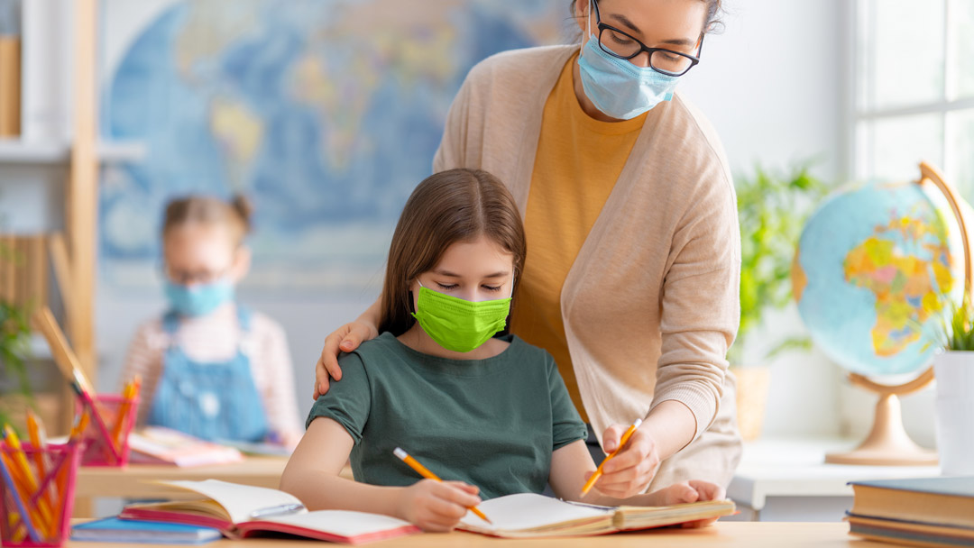 Little girl in school with TImask surgical mask